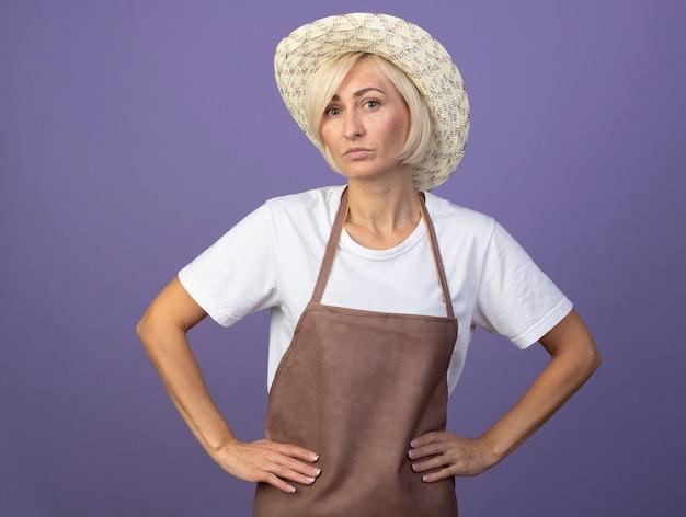 Selbstbewusste blonde gärtnerin mittleren alters in uniform mit hut, die die hände an der taille hält