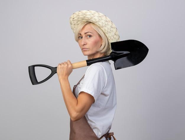 Selbstbewusste blonde gärtnerin mittleren alters in uniform mit hut, die in der profilansicht steht und auf die vorderseite schaut, die spaten auf der schulter isoliert auf weißer wand hält