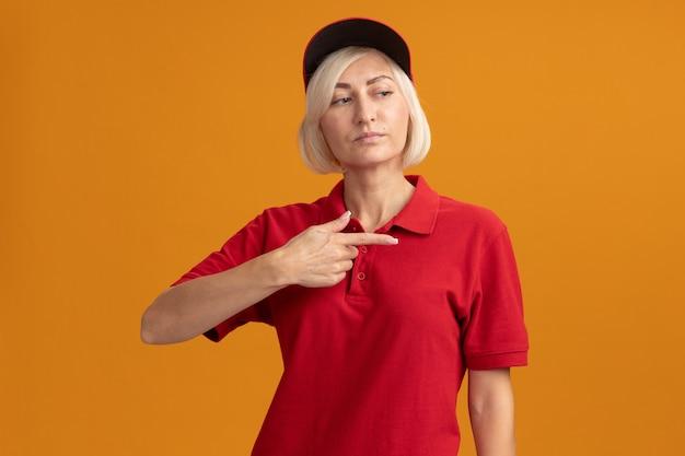 Selbstbewusste blonde lieferfrau mittleren alters in roter uniform und mütze, die auf die seite schaut und zeigt