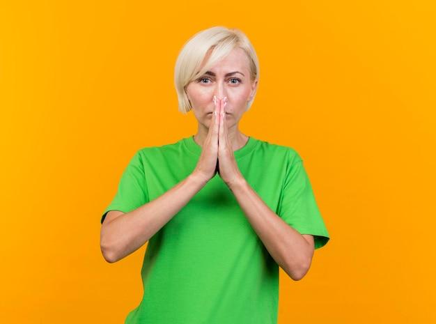 Selbstbewusste blonde slawische frau mittleren alters, die nach vorne schaut, hält hände zusammen in gebetsgeste vor mund lokalisiert auf gelber wand mit kopienraum