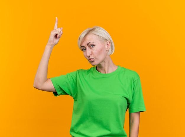 Selbstbewusste blonde slawische frau mittleren alters, die nach vorne zeigt, lokalisiert auf gelber wand mit kopienraum
