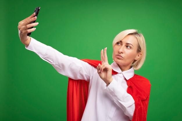 Selbstbewusste blonde superheldin mittleren alters im roten umhang, die ein friedenszeichen macht, das selfie macht