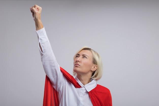Selbstbewusste blonde superheldin mittleren alters in rotem umhang, die die faust hebt und sie betrachtet