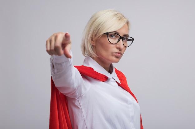 Selbstbewusste blonde superheldin mittleren alters in rotem umhang mit brille, die in der profilansicht steht und isoliert auf weiße wand mit kopienraum zeigt