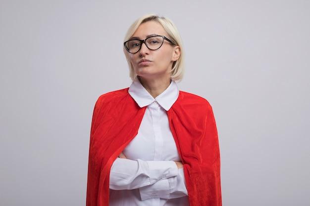 Selbstbewusste blonde superheldin mittleren alters in rotem umhang mit brille, die mit geschlossener haltung isoliert auf weißer wand mit kopierraum steht