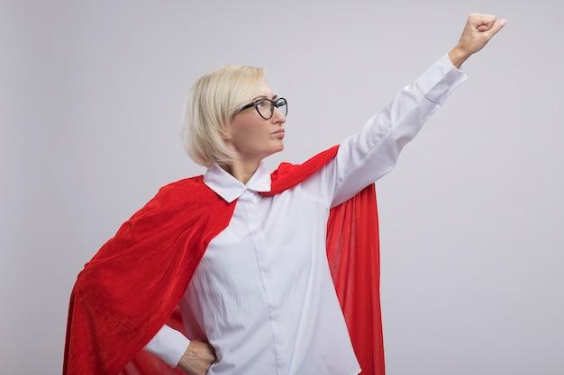 Selbstbewusste blonde superheldin mittleren alters in rotem umhang mit brille, die nach oben schaut und superman-geste macht