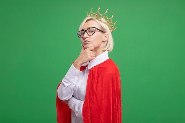 Selbstbewusste blonde superheldin mittleren alters in rotem umhang mit brille und krone, die in der profilansicht steht und die hand auf das kinn legt, isoliert auf grüner wand mit kopierraum