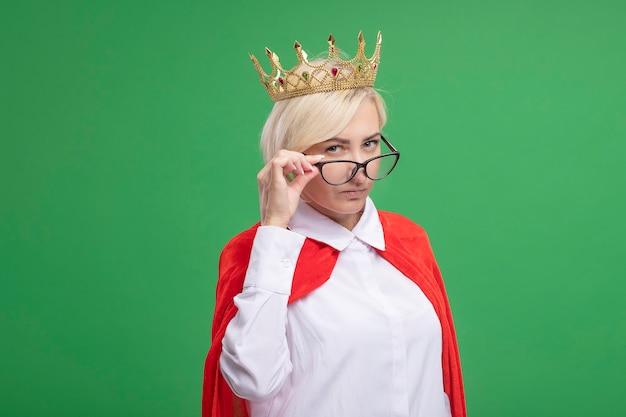 Selbstbewusste blonde superheldin mittleren alters in rotem umhang mit brille und kronengreifender brille