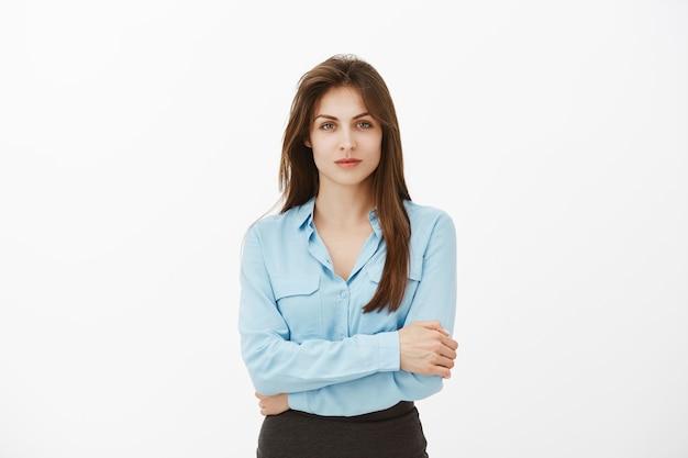 Selbstbewusste brünette geschäftsfrau posiert im studio