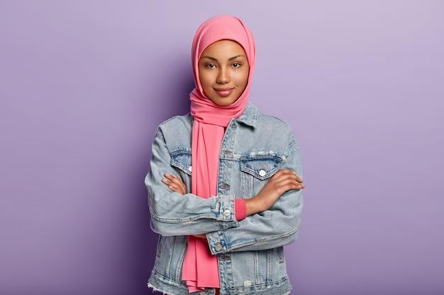 Selbstbewusste dunkelhäutige frau hat muslimische religiöse sicht, hält die arme verschränkt, trägt rosa kopftuch und jeansmantel, isoliert über lila wand, hört nachrichten mit interesse