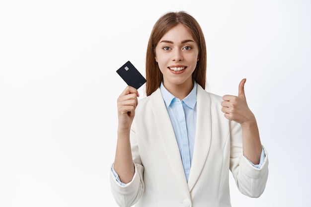 Selbstbewusste, erfolgreiche geschäftsfrau zeigt plastikkreditkarte und daumen hoch, lächelt zufrieden, empfiehlt bank, steht über weißer wand