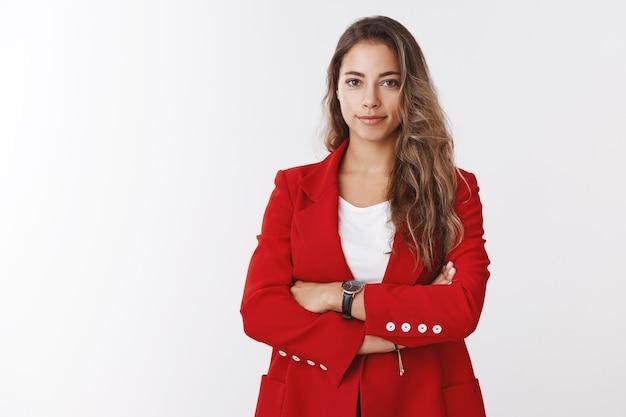 Selbstbewusste, erfolgreiche, gut aussehende, geschickte unternehmerin, die eine rote jacke trägt, die arme über der brust lächeln, entschlossen lächeln, selbstbewusst aussehen und die mitarbeiter im büro überprüfen