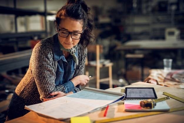 Selbstbewusste ernsthafte attraktive professionelle architektin, die sich gegen den schreibtisch lehnt und in das neue projekt mit notizen, tablette und linealen auf dem tisch in der stoffstelle schaut.