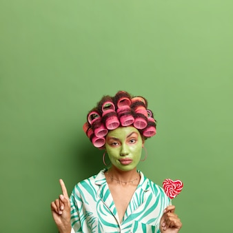 Selbstbewusste ernsthafte frau wendet haarrollen an und hält leckeren lutscher. schönheitsgesichtsbehandlungen in pyjama-posen gegen grüne wand zeigen nach oben. hautpflege und haarstyling