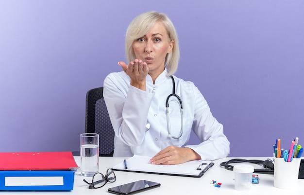 Selbstbewusste erwachsene ärztin in medizinischer robe mit stethoskop, die am schreibtisch mit bürowerkzeugen sitzt und einen kuss mit der hand sendet, isoliert auf lila wand mit kopierraum