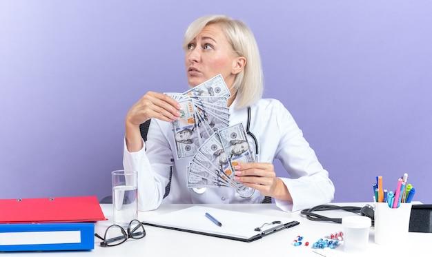 Selbstbewusste erwachsene ärztin in medizinischer robe mit stethoskop, die am schreibtisch mit bürowerkzeugen sitzt und geld hält und auf die seite isoliert auf lila wand mit kopienraum schaut