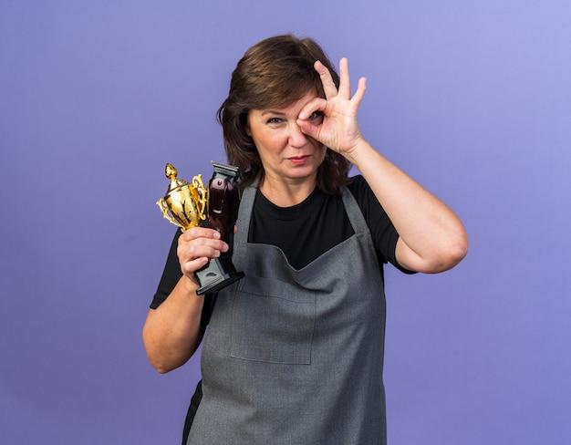 Selbstbewusste erwachsene friseurin in uniform, die haarschneidemaschine und gewinnerpokal hält und nach vorne durch die finger schaut, die auf lila wand mit kopierraum isoliert sind