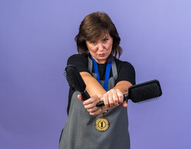 Selbstbewusste erwachsene friseurin in uniform mit goldener medaille um den hals, die kämme isoliert auf lila wand mit kopienraum hält