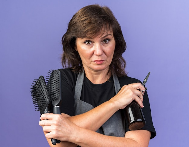 Selbstbewusste erwachsene friseurin in uniform mit kämmen, sprühflasche und schere isoliert auf lila wand mit kopierraum