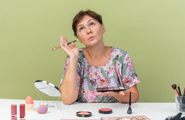 Selbstbewusste erwachsene kaukasische frau, die am tisch mit make-up-tools sitzt und lidschatten-palette und make-up-pinsel nach oben hält
