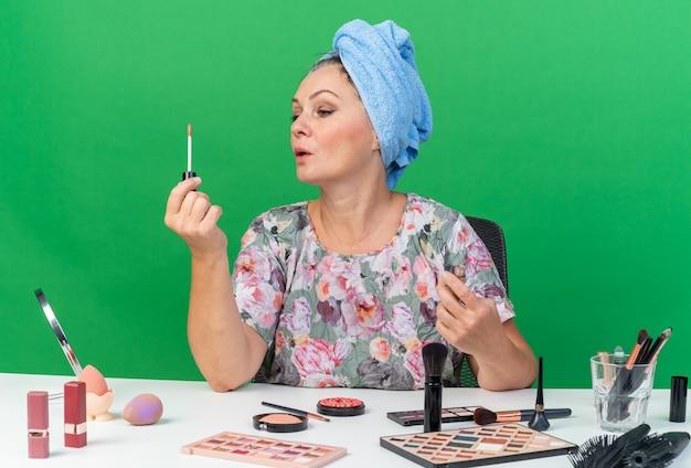 Selbstbewusste erwachsene kaukasische frau mit eingewickeltem haar in handtuch, die am tisch mit make-up-tools sitzt und lipgloss hält und betrachtet