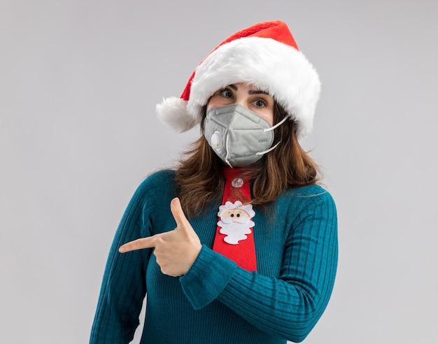 Selbstbewusste erwachsene kaukasische frau mit weihnachtsmütze und weihnachtsmann-krawatte mit medizinischer maske, die auf die seite zeigt, die auf weißer wand mit kopienraum isoliert ist isolated