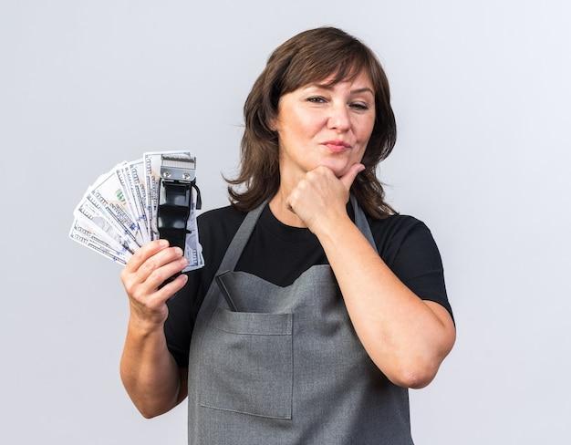 Selbstbewusste erwachsene kaukasische friseurin in uniform, die haarschneidemaschine mit geld hält und das kinn isoliert auf weißem hintergrund mit kopienraum hält