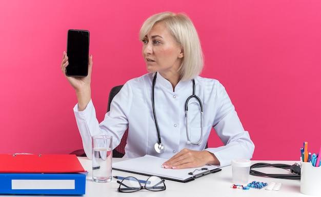 Selbstbewusste erwachsene slawische ärztin in medizinischer robe mit stethoskop am schreibtisch sitzend mit bürowerkzeugen, die das telefon auf rosafarbenem hintergrund mit kopienraum halten und betrachten