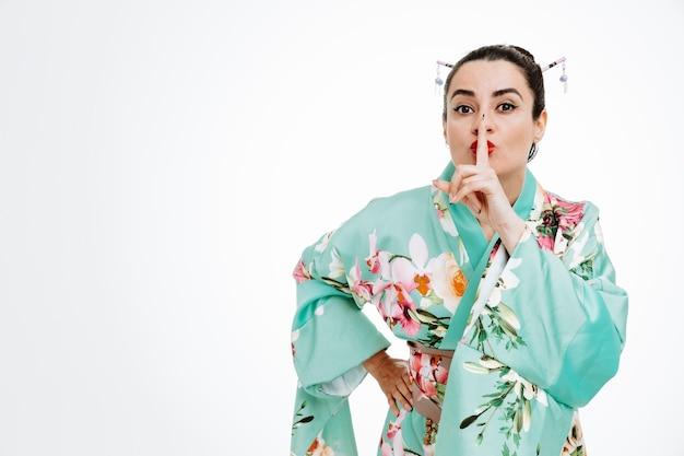 Selbstbewusste frau im traditionellen japanischen kimono, die eine stillegeste mit dem finger auf den lippen auf weiß macht