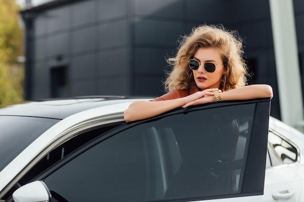 Selbstbewusste frau in formeller kleidung, die draußen in der nähe ihres weißen autos posiert