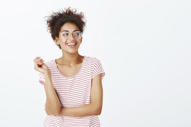 Selbstbewusste frau mit afro-frisur, die im studio aufwirft