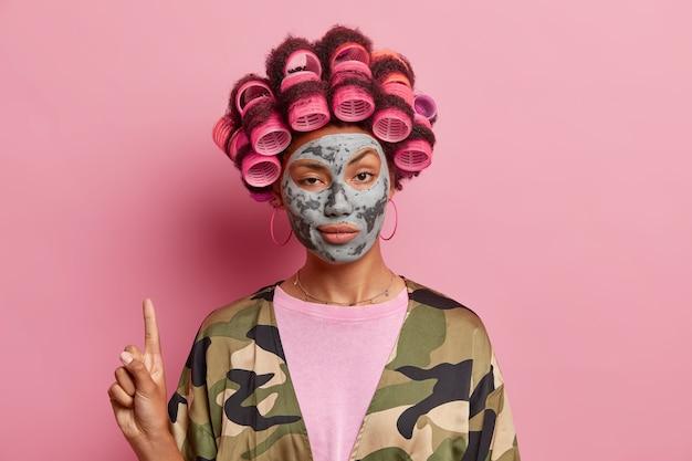 Selbstbewusste frau zeigt oben auf dem kopierraum, wendet haarrollen an und tongesichtsmaske zeigt schönheitsprodukte, die in häuslicher kleidung einzeln über rosafarbener wand gekleidet sind. kosmetikkonzept