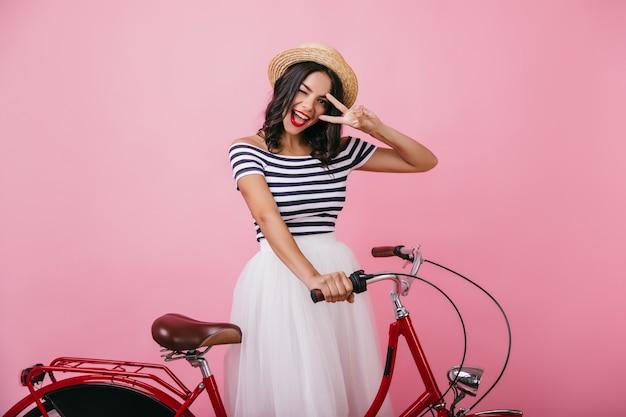 Selbstbewusste gebräunte frau, die mit fahrrad aufwirft und glück ausdrückt. innenfoto des debonair-mädchens im romantischen outfit, das spaß hat.