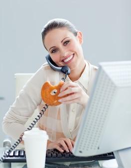 Selbstbewusste geschäftsfrau am telefon eine donnel essend