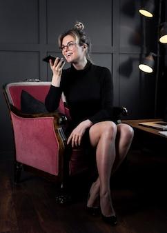 Selbstbewusste geschäftsfrau, die im büro am telefon spricht