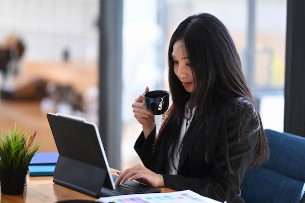 Selbstbewusste geschäftsfrau, die kaffeetasse hält und durch online-informationen über digitale tablets im modernen büro scrollt.