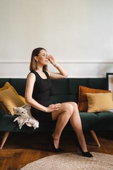 Selbstbewusste geschäftsfrau mit brille in einem schwarzen klassischen kleid, die in einer modernen wohnung auf einer couch sitzt