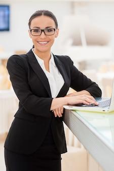 Selbstbewusste geschäftsfrau. schöne junge frau in formeller kleidung, die am laptop arbeitet und lächelt, während sie sich an der bartheke lehnt