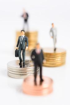 Selbstbewusste geschäftsleute der miniatur stehen auf silbermünzen, die auf weiß isoliert werden
