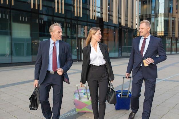 Selbstbewusste geschäftsleute, die mit gepäck reisen, zum hotel gehen, koffer rollen, reden. vorderansicht. geschäftsreise- oder unternehmenskommunikationskonzept