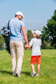 Selbstbewusste golfspieler. rückansicht des jungen mannes und seines sohnes, die händchen halten und sich beim gehen auf dem golfplatz ansehen