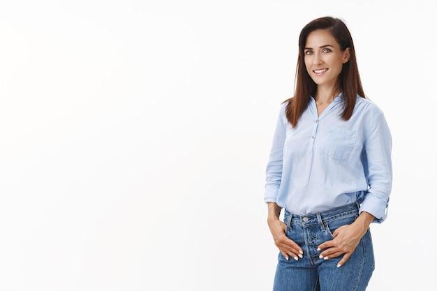 Selbstbewusste, gutaussehende frau startet start-up, hält sich an den jeanstaschen, dreht sich vorn erfreut selbstbewusst, durchsetzungsfähiger sieg, erzielt zielstrebig das beste ergebnis, steht glückliche weiße wand
