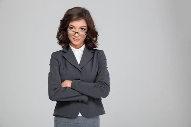 Selbstbewusste hübsche junge lockige geschäftsfrau in brille und grauer jacke, die mit verschränkten armen steht