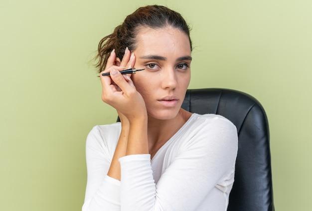 Selbstbewusste hübsche kaukasische frau, die am tisch mit make-up-tools sitzt, die eyeliner einzeln auf olivgrüner wand mit kopienraum aufträgt