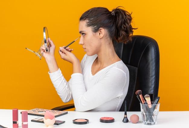 Selbstbewusste hübsche kaukasische frau, die am tisch mit make-up-tools sitzt, die make-up-pinsel hält und den spiegel einzeln auf oranger wand mit kopierraum betrachtet