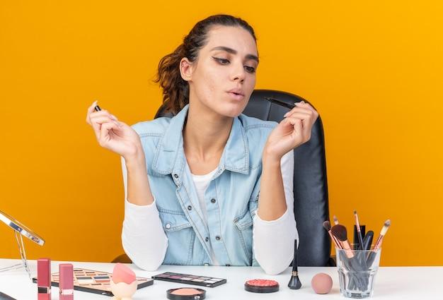 Selbstbewusste hübsche kaukasische frau, die am tisch mit make-up-tools sitzt und eyeliner anschaut