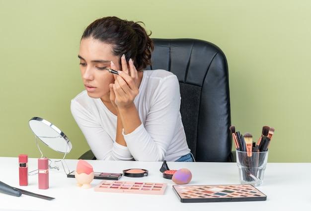 Selbstbewusste, hübsche kaukasische frau, die am tisch mit make-up-tools sitzt und eyeliner anwendet und auf den spiegel schaut, der auf olivgrüner wand mit kopienraum isoliert ist?