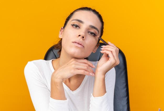 Selbstbewusste, hübsche kaukasische frau, die am tisch mit make-up-tools sitzt und eyeliner hält, isoliert auf oranger wand mit kopierraum