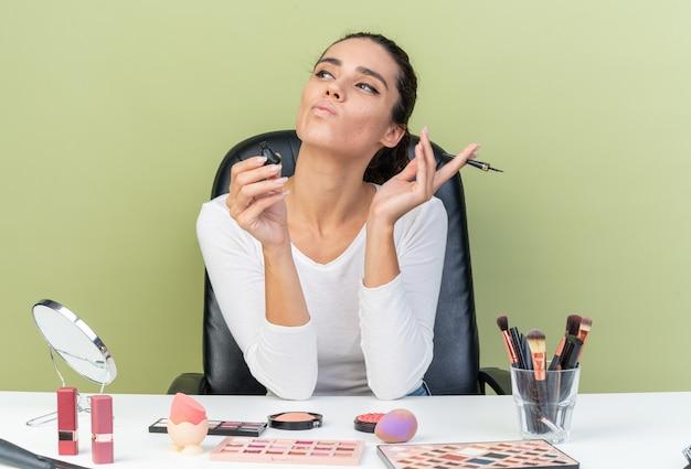 Selbstbewusste hübsche kaukasische frau, die am tisch mit make-up-tools sitzt und eyeliner hält und auf die seite schaut