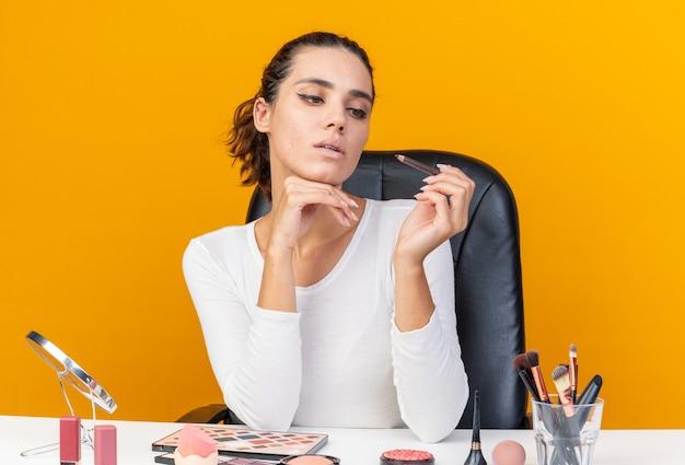 Selbstbewusste hübsche kaukasische frau, die am tisch mit make-up-tools sitzt und eyeliner hält und betrachtet